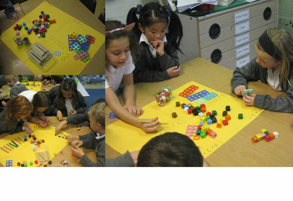 Working together using maths equipment to solve multiplication problems.