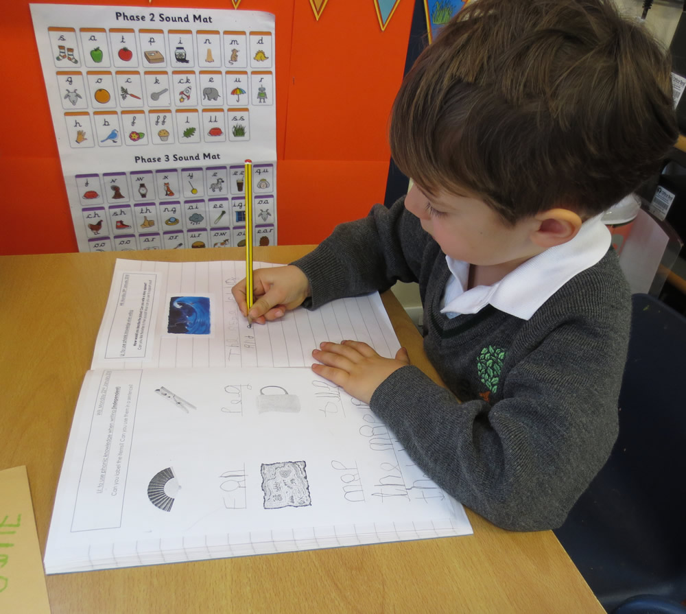 Using phonics knowledge to write about a picture.