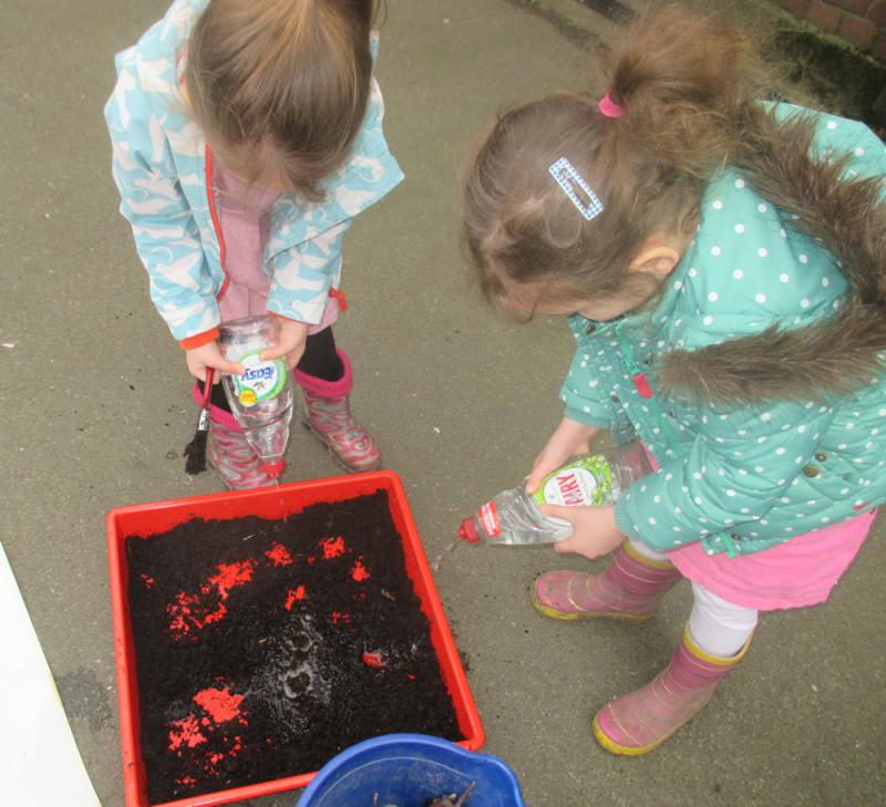 Nursery children mixed earth and water to make thick oozy mud.